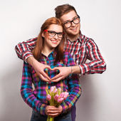 Young couple in love make a heart and hands are holding a bouquet of tulips — Stock Photo