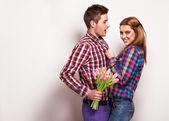 Jong paar in liefde maken een hart en handen houden een boeket van tulpen — Stockfoto