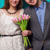 Beautiful couple in love with flowers tulips.Valentine's Day — Zdjęcie stockowe