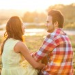 Stock Photo: Back view of young happy couple sitting on river at sunset