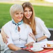 Adult mother and daughter drinking tea or coffee and talking outdoors. — Stock Photo #40385317