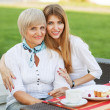 Adult mother and daughter drinking tea or coffee and talking outdoors. — Stock Photo #40385345