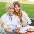Stock Photo: Adult mother and daughter drinking teor coffee and talking outdoors.