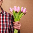 Stock Photo: Mclothing hipster holding bouquet of flowers