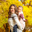 Stock Photo: Young mother and her toddler girl have fun in autumn