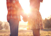 Young couple in love walking in the autumn park holding hands — Stock Photo