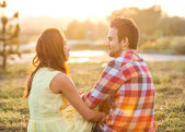 Back view of young happy couple sitting on river at sunset — Stock Photo