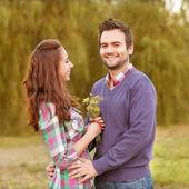 Ungt par i kärlek promenader i parken hösten nära floden. — Stockfoto