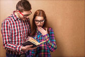 Young couple in clothes and stylish hipster glasses reading a book. — Stock Photo