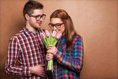 Portrait of young couple in love with flowers tulips — Stock Photo