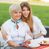 Adult mother and daughter drinking tea or coffee and talking outdoors. — Stock Photo