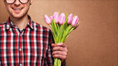 Man clothing hipster holding a bouquet of flowers — Stock Photo