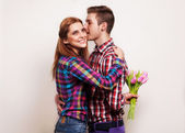 Young couple in love holding a bouquet of tulips. — Stock Photo