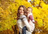 Genç anne ve çocuk kızı sonbaharda eğlenin — Stok fotoğraf