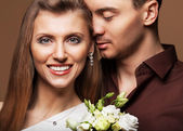 Couple in love with a bouquet of flowers are close to each other — Stok fotoğraf