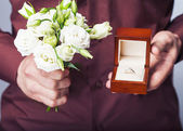 Holding ring box and a bouquet of flowers — Stock Photo