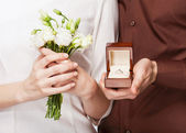 Wedding couple holding ring box and a bouquet of flowers — Foto de Stock