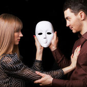 Fashion Happy Couple in Love holding a white mask face. — Foto de Stock