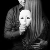 Fashion man holding a white mask face. Psychological concept. — Stock Photo