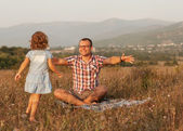 Father and daughter on the field in the mountains happy — Stock Photo