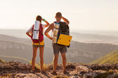 Hikers with backpacks enjoying valley view from top of a mountai — Stock Photo