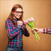 Girl wearing hipster surprised donation of a bouquet of flowers — Stock Photo