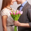 Couple in love with a bouquet of tulips are close to each other — Stock Photo #43937143