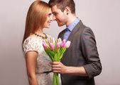 Couple in love with a bouquet of tulips are close to each other — Foto Stock