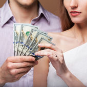 Loving couple are holding a large sum of money. — Stock Photo