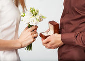 Wedding couple holding ring box and a bouquet of flowers — Stock fotografie