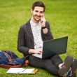 A young man with laptop outdoor — Stock Photo