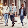 Three Young male fashion metraseksuals shop. Men shopping walk. — Stock Photo