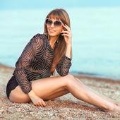 美しい女性の海辺で日光浴 — ストック写真