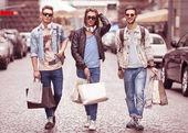 Three Young male fashion metraseksuals shop. Men shopping walk. — Photo