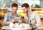 Two young students using tablet computer in cafe — Stock Photo