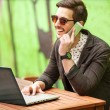 Young man drinking coffee in cafe and using tablet computer — Stock Photo #46395339