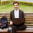A smiling man with laptop outdoor — Stock Photo