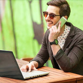 Young man drinking coffee in cafe and using tablet computer — Stock Photo