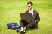 Young fashion male student sitting on grass in park — Stock Photo