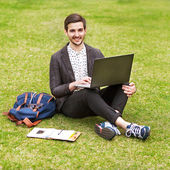 Young man using his laptop on the grass and makes notes in a not — Stock Photo