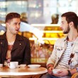 Two young hipster guy sitting in a cafe chatting and drinking coffee smiling — Stock Photo
