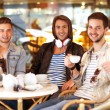 Young hipster guy sitting in a cafe chatting and drinking coffe — Stock Photo