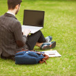 Young fashion male student sitting on grass in park — Stock Photo #46407869