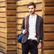 Portrait of young beautiful fashionable man against wooden wall. — Stock Photo #46409459