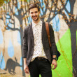 Attractive young male model posing on green wall outdoors — ストック写真