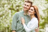 Couple amoureux dans la floraison des pommiers de jardin, souriant — Foto Stock