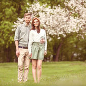 Couple in love in blooming apple trees garden, smiling — Stock Photo