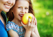 Mother and her child enjoy the early spring, eating apple, happy — Stock Photo