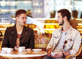 Two young hipster guy sitting in a cafe chatting and drinking coffee smiling — Foto Stock