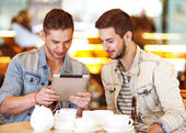 Two young men using tablet computer in cafe — Stockfoto